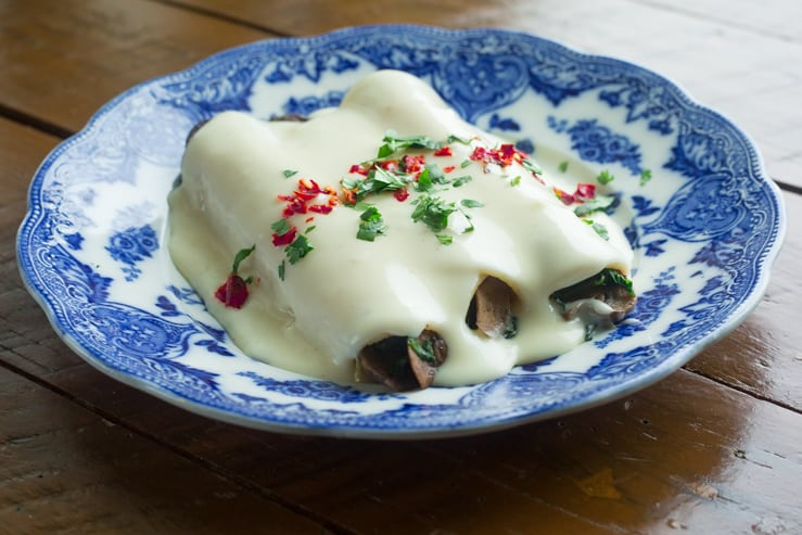 Spinach and Mushroom Enchiladas with Monterey Jack Cream Sauce on a blue antique plate